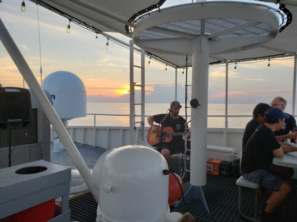"First officer Fraser Retson playing guitar during an ""open mic"" session on the upper deck of the Pressure Drop"